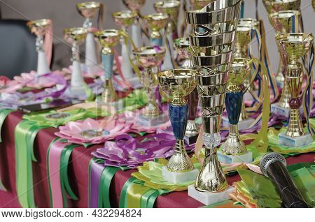 Various Sports Trophies, Awards Ribbons And A Microphone On The Table. Group Of Golden Sports Cups T