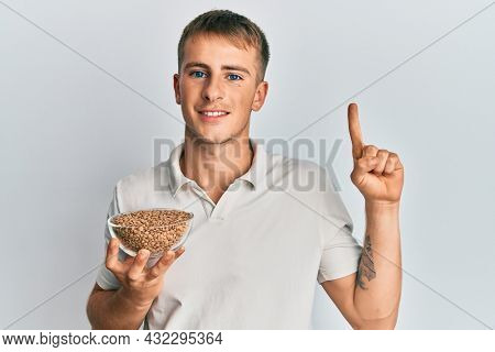 Young caucasian man holding lentils bowl smiling with an idea or question pointing finger with happy face, number one