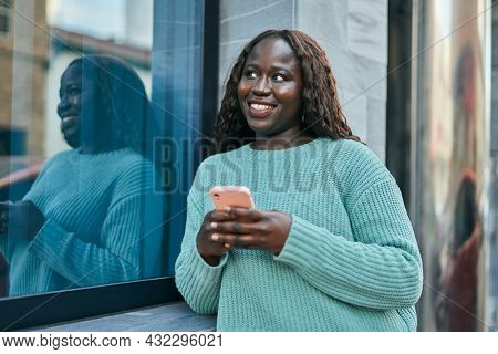 Young african woman smiling happy using smartphone leaning on the wall