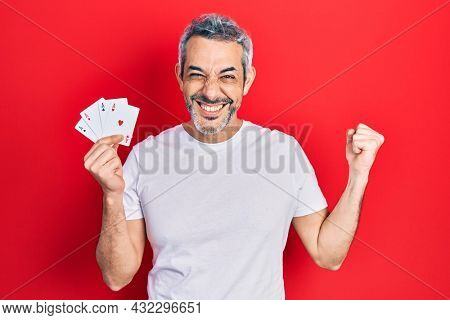 Handsome middle age man with grey hair holding poker cards screaming proud, celebrating victory and success very excited with raised arm