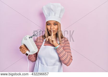 Beautiful hispanic woman holding pastry blender electric mixer asking to be quiet with finger on lips. silence and secret concept.