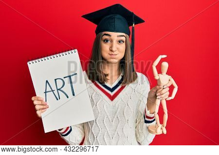 Young brunette girl graduated on art puffing cheeks with funny face. mouth inflated with air, catching air.