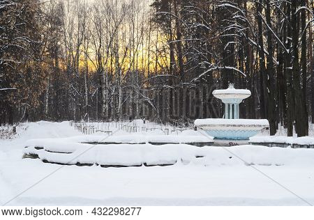 Vintage Fountain In Public Park At Winter Time. Snow On Trees. Sunset.