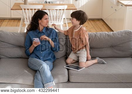 Tired Mother Try To Read Messages Or Surf Internet On Smartphone After Work Sitting On Couch With Di