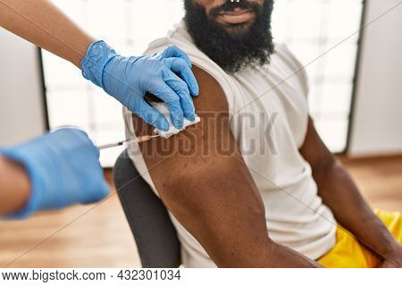 Hands of nurse woman injecting covid-19 vaccine to african amercian man at the clinic.
