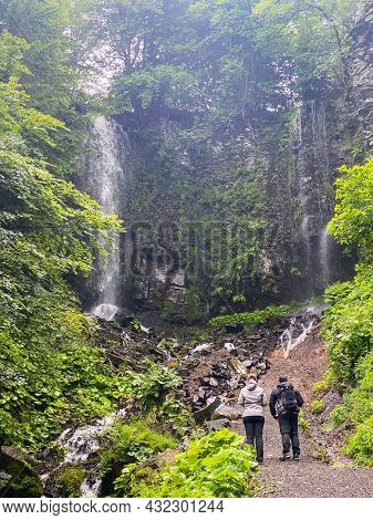 two hikers looking Saut du Loup waterfall, Mont-Dore, Auvergne, France