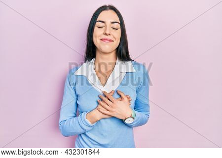 Beautiful woman with blue eyes standing over pink background smiling with hands on chest with closed eyes and grateful gesture on face. health concept.