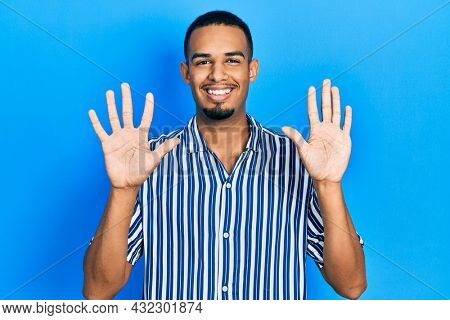 Young african american man wearing casual clothes showing and pointing up with fingers number ten while smiling confident and happy.