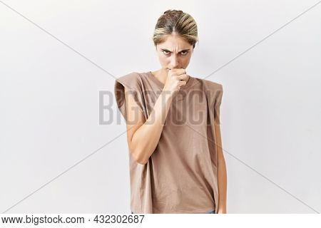 Young blonde woman standing over isolated background feeling unwell and coughing as symptom for cold or bronchitis. health care concept.