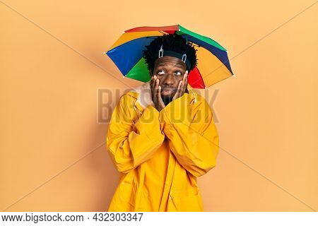 Young african american man wearing yellow raincoat tired hands covering face, depression and sadness, upset and irritated for problem