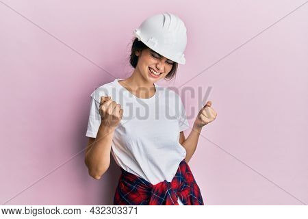 Young caucasian woman wearing hardhat very happy and excited doing winner gesture with arms raised, smiling and screaming for success. celebration concept.