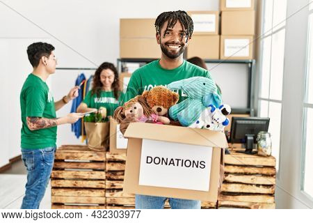 Group of young volunteers working at charity center. Man smiling happy and holding box with toys to donate.