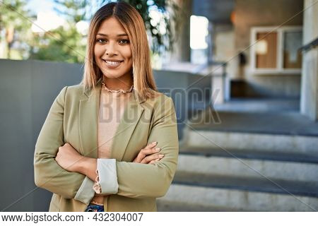Young latin woman smiling confident at street