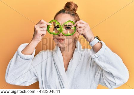 Young blonde woman wearing bathrobe holding green pepper over eyes puffing cheeks with funny face. mouth inflated with air, catching air.