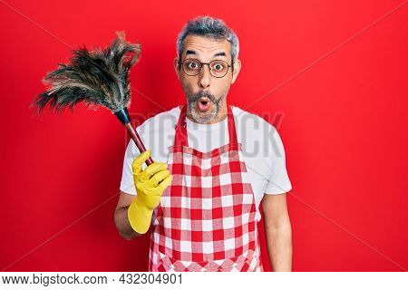 Handsome middle age man with grey hair wearing apron holding cleaning duster scared and amazed with open mouth for surprise, disbelief face