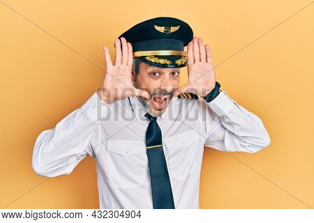 Handsome middle age man with grey hair wearing airplane pilot uniform smiling cheerful playing peek a boo with hands showing face. surprised and exited