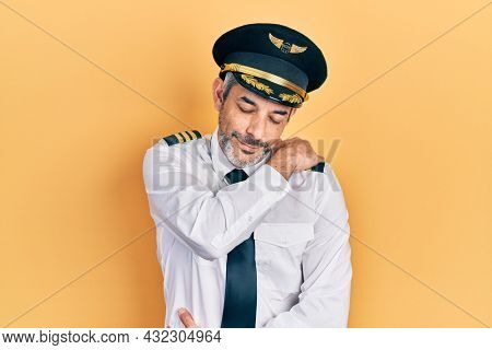 Handsome middle age man with grey hair wearing airplane pilot uniform hugging oneself happy and positive, smiling confident. self love and self care