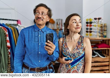 Middle age interracial couple at retail shop using smartphone smiling looking to the side and staring away thinking.