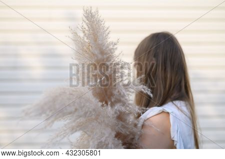 Woman Holding A Beautiful Bouquet With Pampas Grass On Beige Background. Front View. Faceless Concep