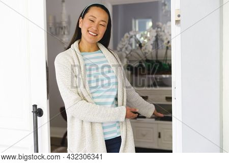 Portrait of smiling asian woman standing at door and inviting visitor to room. hospitality and welcoming guests at home.