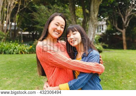 Portrait of happy asian mother embracing her daughter and smiling outdoors in garden. family enjoying leisure time together at home.