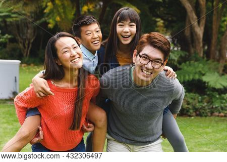Portrait of happy asian parents, son and daughter smiling outdoors in garden. family enjoying leisure time together at home.
