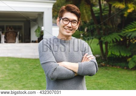 Portrait of happy asian man wearing glasses smiling in garden outside family home. enjoying leisure time alone at home.