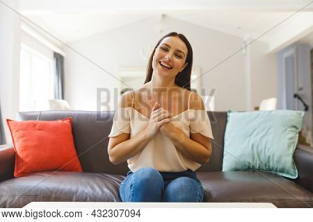 Caucasian woman sitting on couch having video call in living room, smiling. keeping in touch, leisure time at home with communication technology.