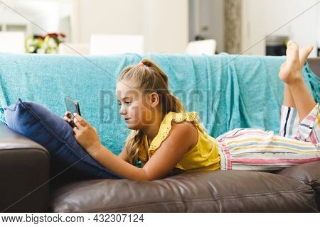 Caucasian girl lying on couch and using tablet in living room. childhood leisure time, fun and discovery at at home using technology.