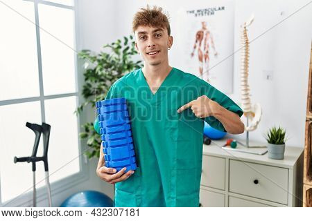 Young caucasian man holding foam roller working at pain recovery clinic pointing finger to one self smiling happy and proud