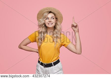 Happy Young Blonde Female In Yellow T Shirt And Straw Hat Pointing Up With Forefinger Against Pink B