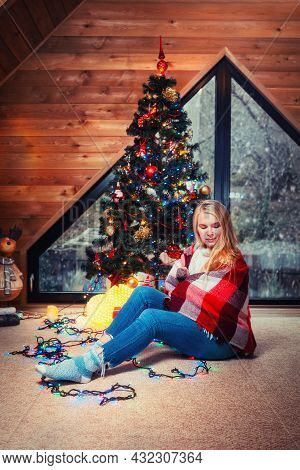 Christmas And New Year. A Young Pretty Woman Wrapped In A Blanket, Posing Against The Background Of
