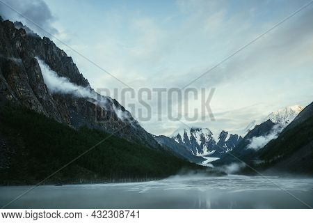 Scenic Alpine Landscape With Snowy Mountain Peak In Golden Sunlight And Mountain Lake In Fog Under C