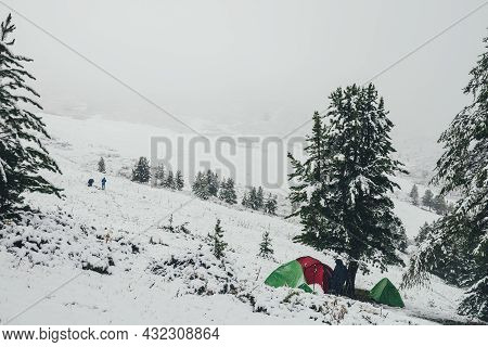 Scenic Winter Landscape With Green Tent And Red Tent On Snowy Hill With Coniferous Trees On Backgrou