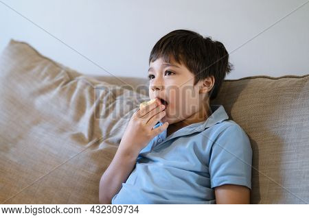 Healthy Mixed Race Child Boy Eating Red Apple While Watching Tv, Happy Young Kid Sitting On Sofa Rel