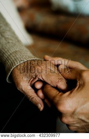 a young caucasian man holds the hand of a senior caucasian woman with affection