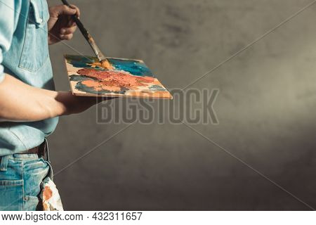 Man painter holding paint palette with paint brush. Young artist and paintbrush painting in creative studio