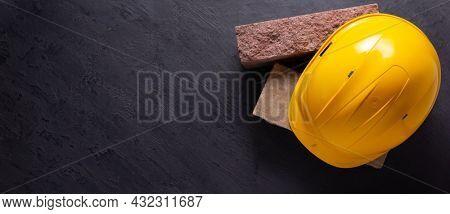 Construction hardhat at brick on black background. Helmet and bricks