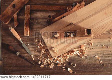 Plane jointer carpenter or joiner tool and wood shavings. Woodworking tools on wooden table. Carpentry workshop