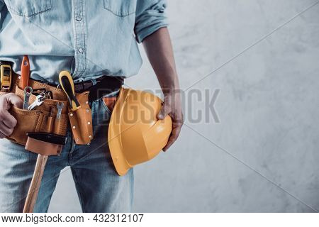 Worker man holding construction helmet tool near concrete or cement wall. Male hand and hard hat for house room renovation. Home renovation concept