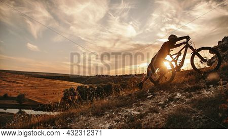 Side View Of Unrecognizable Sportive Cyclist Climbing Up Hill With Electric Mountain Bike Against Su