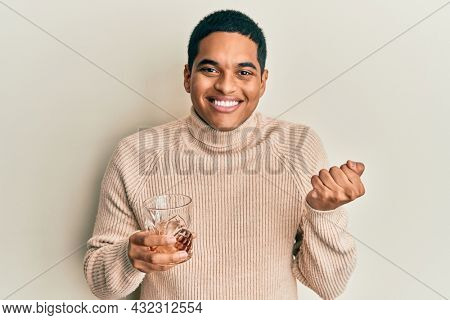 Young handsome hispanic man drinking glass of whisky screaming proud, celebrating victory and success very excited with raised arm