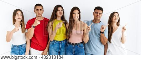 Group of people wearing casual clothes standing over isolated background pointing aside worried and nervous with forefinger, concerned and surprised expression