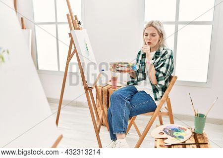 Young artist woman painting on canvas at art studio feeling unwell and coughing as symptom for cold or bronchitis. health care concept.
