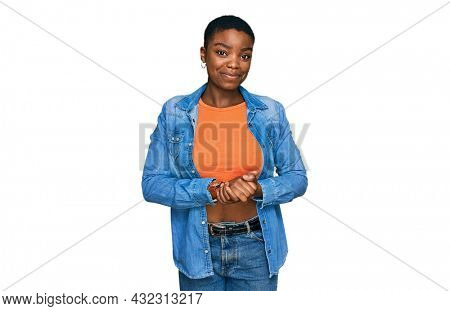 Young african american woman wearing casual clothes with hands together and crossed fingers smiling relaxed and cheerful. success and optimistic