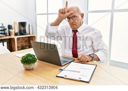 Senior man working at the office using computer laptop making fun of people with fingers on forehead doing loser gesture mocking and insulting.