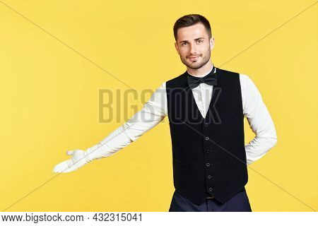 Young Handsome Waiter Doing A Welcome Gesture Over Yellow Background