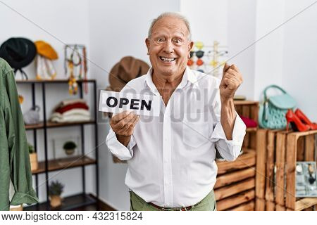 Senior man holding banner with open text at retail shop screaming proud, celebrating victory and success very excited with raised arms
