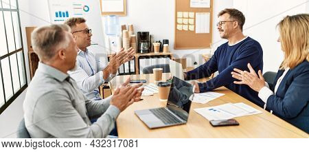 Group of middle age business workers smiling and clapping to partner at the office.