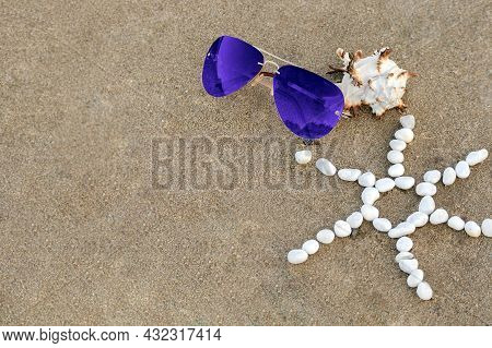 Blue Sunglasses Lie On Sand Beach With Seashell And Sun Made Of White Stones. Concept Summer Holiday